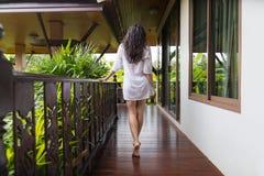 Νέο κορίτσι στο πεζούλι ξενοδοχείων, τροπικές δασικές όμορφες πίσω οπισθοσκόπες θερινές διακοπές γυναικών Στοκ Εικόνες