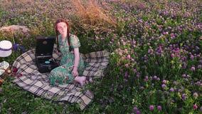 Νέο κορίτσι στο πικ-νίκ στο λιβάδι που ακούει το αρχείο εκλεκτής ποιότητας gramophone φιλμ μικρού μήκους