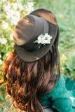Νέο κορίτσι στο πράσινα φόρεμα και το μαύρο καπέλο στοκ φωτογραφία