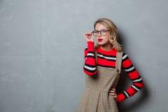 Νέο κορίτσι στο φόρεμα και το ριγωτό πουλόβερ στοκ εικόνα με δικαίωμα ελεύθερης χρήσης