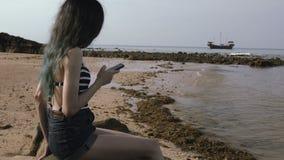 Νέο κορίτσι τουριστών που χρησιμοποιεί το κινητό τηλέφωνο στην παραλία κοντά στη θάλασσα με την όμορφη βάρκα απόθεμα βίντεο
