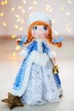 Νέο κορίτσι χιονιού κοριτσιών χιονιού έτους παιχνιδιών δώρων σε ένα υπόβαθρο των φω'των στοκ εικόνες με δικαίωμα ελεύθερης χρήσης