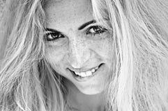 Νέο κορίτσι Ablond με τις φακίδες που χαμογελά στο χείλι δαγκώματος καμερών Στοκ Εικόνα