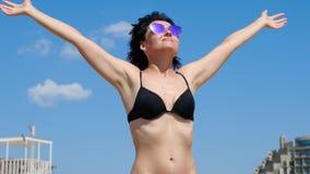 Νέο κορίτσι brunette με τα αυξημένα χέρια προς έναν μπλε ουρανό μια ηλιόλουστη ημέρα φιλμ μικρού μήκους