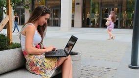 Νέο κορίτσι brunette που μελετά και που χρησιμοποιεί το lap-top στο πάρκο Υπαίθριος, καλοκαίρι φιλμ μικρού μήκους