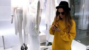 Νέο κορίτσι brunette που ψωνίζει on-line Το κορίτσι επιλέγει τα ενδύματα στο κατάστημα και το αγοράζει μέσω του τηλεφώνου on-line απόθεμα βίντεο