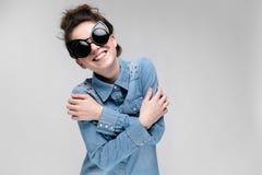 Νέο κορίτσι brunette στα μαύρα γυαλιά Γυαλιά γατών Η τρίχα μαζεύεται σε ένα κουλούρι Το κορίτσι δίπλωσε τα όπλα της Το κορίτσι εί Στοκ φωτογραφία με δικαίωμα ελεύθερης χρήσης