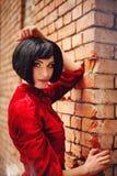 Νέο κορίτσι brunette στο εκλεκτής ποιότητας ρομαντικό κόκκινο φόρεμα κοντά στον τοίχο Στοκ Εικόνες