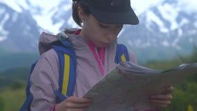 Νέο κορίτσι Hipster με το σακίδιο πλάτης στην αιχμή του βουνού που φαίνεται χάρτης Ταξιδιώτης τουριστών στην άποψη τοπίων κοιλάδω απόθεμα βίντεο