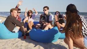 Νέο κορίτσι hipster που καταγράφει ένα βίντεο ή που παίρνει τις εικόνες της ομάδας φίλων που κάθονται στα easychairs στην παραλία απόθεμα βίντεο