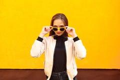Νέο κορίτσι hipster που κρατά τα κίτρινα γυαλιά ηλίου στον πορτοκαλή τοίχο ύφος αστικό Στοκ Εικόνες