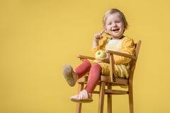 Νέο κοριτσάκι στο κίτρινο φόρεμα στο κίτρινο υπόβαθρο στοκ φωτογραφία