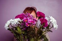 Νέο κρύψιμο γυναικών πίσω από μια ανθοδέσμη των λουλουδιών Στοκ Εικόνες