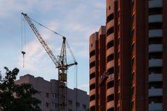Νέο κτήριο τούβλου οικοδόμησης πύργος γερανών Στοκ εικόνα με δικαίωμα ελεύθερης χρήσης