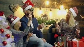 Νέο κόμμα έτους στο σπίτι Άτομο και δύο κορίτσια γιορτάζουν τα Χριστούγεννα, τη σαμπάνια κατανάλωσης και τα φω'τα σπινθηρίσματος  απόθεμα βίντεο