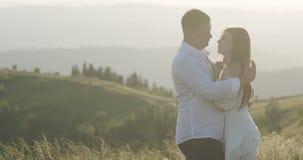 Νέο λατρευτό αγκάλιασμα ζευγών, που φιλά το ένα το άλλο στην πράσινη πυκνή περιοχή βουνών Καλοκαίρι, ηλιοβασίλεμα Στόχοι ζεύγους απόθεμα βίντεο