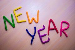 Νέο μήνυμα έτους από το ζωηρόχρωμο φωτεινό plasticine σε ένα ελαφρύ ξύλινο υπόβαθρο Στοκ Εικόνες