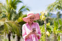 Νέο μήνυμα γυναικών με το έξυπνο τηλέφωνο κυττάρων πέρα από τροπικό να κουβεντιάσει κοριτσιών δασών και μπλε ουρανού όμορφο on-li Στοκ Εικόνα