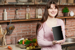 Νέο μαγείρεμα γυναικών στην κουζίνα στο σπίτι Το κορίτσι στην κουζίνα κρατά μια ταμπλέτα και εξετάζει τη κάμερα Στοκ Φωτογραφίες