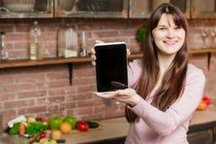Νέο μαγείρεμα γυναικών στην κουζίνα στο σπίτι Το κορίτσι στην κουζίνα κρατά μια ταμπλέτα και εξετάζει τη κάμερα Στοκ εικόνα με δικαίωμα ελεύθερης χρήσης