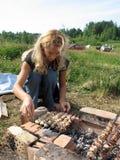 Νέο μακρυμάλλες ξανθό ψήνοντας κρέας γυναικών στην πυρκαγιά στοκ εικόνες