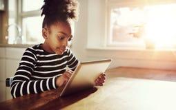 Νέο μαύρο κορίτσι που κοιτάζει βιαστικά σε ένα ταμπλέτα-PC Στοκ φωτογραφία με δικαίωμα ελεύθερης χρήσης