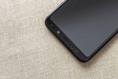 Νέο μαύρο σύγχρονο κινητό τηλέφωνο στο ελαφρύ διαστημικό υπόβαθρο αντιγράφων υφασμάτων Σύγχρονα τεχνολογία, επικοινωνία και σχέδι στοκ φωτογραφία με δικαίωμα ελεύθερης χρήσης