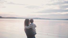 Νέο μικρό παιδί εκμετάλλευσης γυναικών brunette στην ακτή της παραλίας Φιλί μητέρων ο γιος της, που δείχνει με το δάχτυλο στον ορ απόθεμα βίντεο
