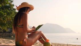 Νέο μικτό κορίτσι τουριστών φυλών χρησιμοποιώντας την κινητή συσκευή ταμπλετών και κάνοντας ηλιοθεραπεία στην τροπική παραλία 4K, απόθεμα βίντεο