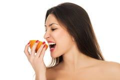 Νέο μισό δαγκωμάτων γυναικών ενός πορτοκαλιού, στο άσπρο υπόβαθρο στοκ φωτογραφία με δικαίωμα ελεύθερης χρήσης