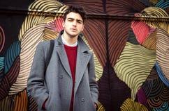Νέο μοντέρνο άτομο που στέκεται μπροστά από το ζωηρόχρωμο τοίχο Στοκ Φωτογραφίες