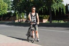 Νέο μοντέρνο άτομο που στέκεται στο δρόμο με το ποδήλατο στην πλάτη Στοκ Εικόνα