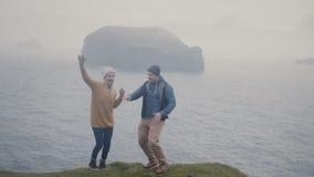 Νέο μοντέρνο ζεύγος που έχει τη διασκέδαση από κοινού Άνδρας και γυναίκα που χορεύουν στην ακτή της θάλασσας στην ομιχλώδη ημέρα απόθεμα βίντεο