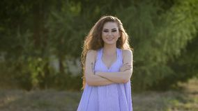 Νέο μοντέρνο κορίτσι με το τίναγμα makeup επικεφαλής και τον κυματισμό μακρυμάλλη στο φυσικό υπόβαθρο απόθεμα βίντεο