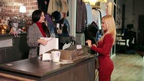 Νέο μοντέρνο κορίτσι σε ένα κατάστημα μόδας, πληρώνει με μια πλαστική πιστωτική κάρτα απόθεμα βίντεο
