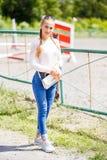 Νέο μοντέρνο κορίτσι στην άσπρα μπλούζα και το τζιν παντελόνι Στοκ εικόνες με δικαίωμα ελεύθερης χρήσης