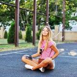 Νέο μοντέρνο κορίτσι στην τοποθέτηση περιστασιακών ενδυμάτων υπαίθρια Στοκ Εικόνες