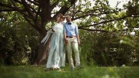 Νέο, μοντέρνο, όμορφο ζευγάρι των newlyweds που περπατούν στο πάρκο απόθεμα βίντεο