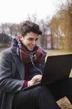 Νέο μοντέρνο texting μήνυμα ανδρών σπουδαστών στο lap-top στο πάρκο Στοκ Φωτογραφίες