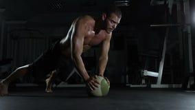 Νέο μυϊκό άτομο που κάνει τη γυμναστική στη γυμναστική με τη σφαίρα απόθεμα βίντεο