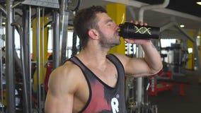 Νέο μυϊκό άτομο που πίνει ένα μπουκάλι νερό φιλμ μικρού μήκους