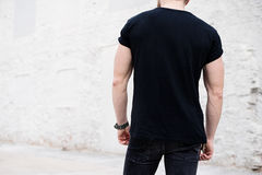 Νέο μυϊκό γενειοφόρο άτομο που φορούν τη μαύρη μπλούζα και τζιν που θέτουν στο κέντρο της σύγχρονης πόλης Κενός συμπαγής τοίχος Στοκ Εικόνες