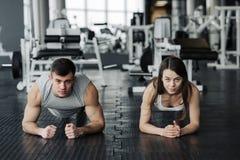 Νέο μυϊκό ζεύγος που κάνει κάνοντας το σκληρό workout στη γυμναστική Να κάνει τη σανίδα στη γυμναστική στοκ εικόνα με δικαίωμα ελεύθερης χρήσης