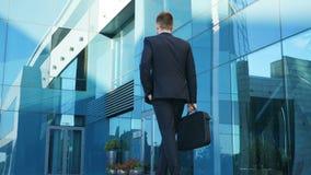 Νέο να ανταλάξει επιχειρηματιών στην εργασία Βέβαιος τύπος στο κοστούμι που είναι στο δρόμο του στο γραφείο Επιχειρησιακό άτομο μ φιλμ μικρού μήκους