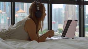 Νέο να βρεθεί γυναικών σε ένα κρεβάτι ακούει τη μουσική στη χρησιμοποίηση lap-top της ασύρματα ακουστικά απόθεμα βίντεο