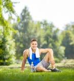 Νέο να είσαι αθλητικών τύπων που κάθεται στη χλόη σε ένα πάρκο Στοκ φωτογραφίες με δικαίωμα ελεύθερης χρήσης