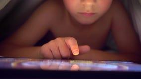 Νέο ξανθό αγόρι κάτω από τις καλύψεις που παίζουν στην ταμπλέτα ένα παιχνίδι στον υπολογιστή φιλμ μικρού μήκους