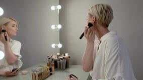 Νέο ξανθό κορίτσι με τη σύντομη συνεδρίαση τρίχας μπροστά από έναν μεγάλο καθρέφτη Εφαρμογή μιας σκόνης στο πρόσωπό της που χρησι απόθεμα βίντεο