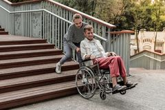 Νέο ξανθό κορίτσι που βοηθά τον ανάπηρο συνεργάτη της στοκ εικόνες