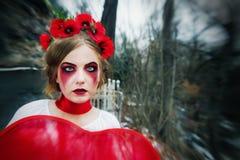 Νέο ξανθό κορίτσι που φωνάζει τα αιματηρά δάκρυα στο νεκροταφείο Στοκ Εικόνα